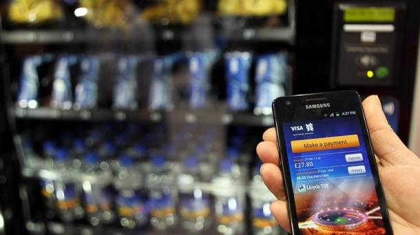 Un empleado muestra como comprar con un móvil con cuenta de Visa, en el MWC.