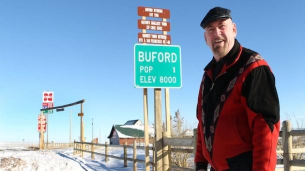 Don Sammons, único habitante de Buford, posa ante el cartel de bienvenida al pueblo: Foto: thefw.