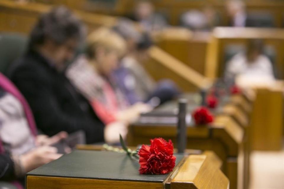 Los parlamentarios de EH Bildu muestran cinco claveles rojos en memoria de los asesinados. EFE
